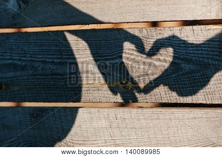 Pregnant Couple Showing Shadow Heart With Fingers