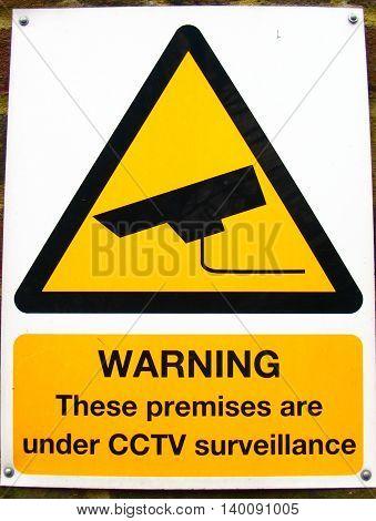 Yellow CCTV camera warning sign close up