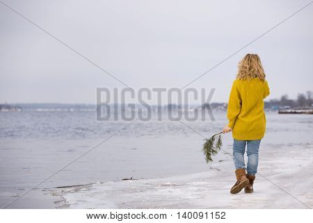 Beautiful blond woman in a yellow sweater and blue jeans walking on the river shore. Happy girl walking on the sand beach. Spring in the city. Enjoying walking outdoors. Snow on the shore.