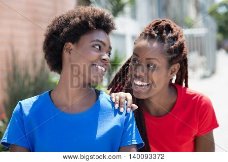 Two beautiful african american woman talking outdoor in city