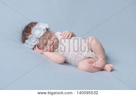 infant girl in a white dress sleeping on a blue background
