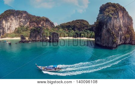Aerial view of clear sea with traditional longtail boats and the rocky crag on the background. Thailand