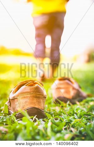 Girl Take Off Her Shoes. Child's Foot Learns To Walk On Grass With Sunlight.
