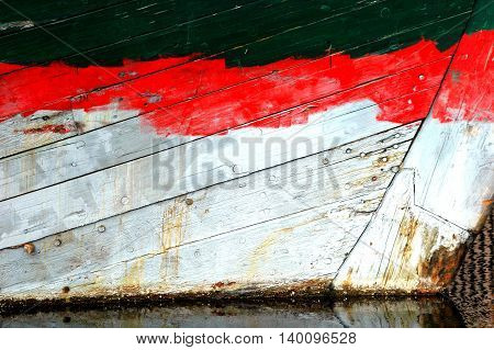 Colorful abstract wooden boat hull on a vessel docked outside.