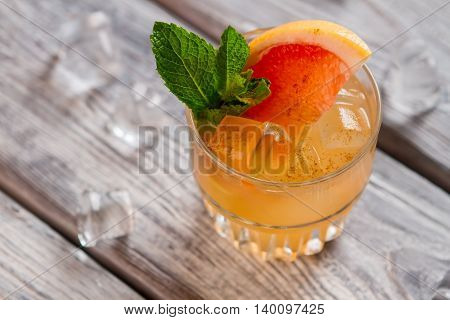 Orange cocktail with ice. Mint and piece of grapefruit. Alcohol mixed with juice. Cobas beverage spiced with cinnamon.