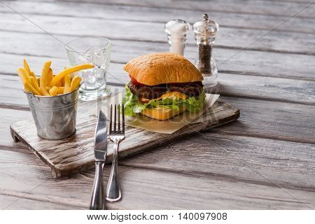 Bucket of fries and cutlery. Burger near a glass. American food cooked in diner. Special recipe of cheeseburger.