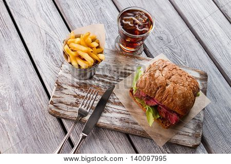 Sandwich and bucket with fries. Cola with ice. Yummy snack served with drink. Don't go around hungry.