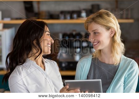 Beautiful business colleague using digital tablet in café