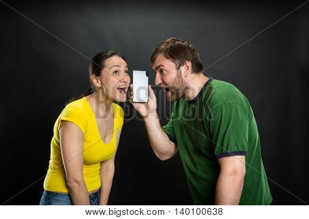 Young couple listening to joke using smartphone over black background