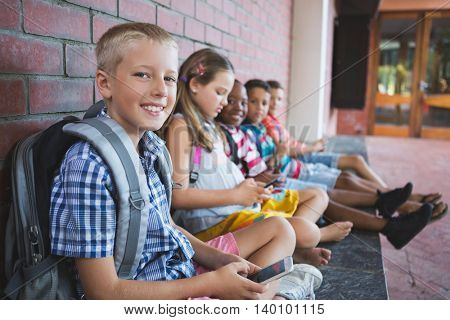 Schoolkids sitting in corridor and using mobile phone at school