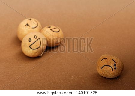 Group of brown ball laughing in the background while the brown ball in front alone,look sad and depressed.Different lighting and focusing to emphasize.Concept of discrimination,bully,mental illness.