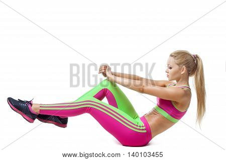 Woman exercising and doing a crunch to work her abs over white isolated background