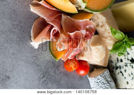 Jambon mix. Ham. Traditional Italian and Spanish salting smoking dry-cured dish - jamon Serrano and prosciutto crudo sliced with melon on grey background. Copy space. Closeup. poster