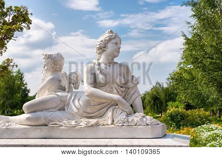 Marble statue of greek goddess with naked breast and cupid in the park