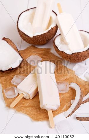 Homemade coconut popsicles on a paper with ice on a white wooden background