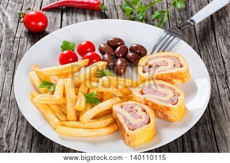 Tasty french fries sprinkled with parsley on white dish with baked cheese meat Roll-Ups kalamata olives and cherry tomatoes view from above blank space left close-up. selective focus