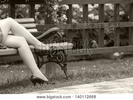female legs in black sandals in the summer, on the bench, next to a fence with flowers, a woman short dress, legs crossed, black and white photo,  bench with armrests carved