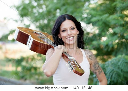 Brunette pretty woman with a clasic guitar