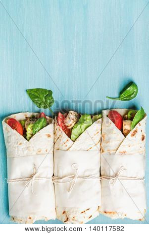 Healthy lunch snack. Three tortilla wraps with grilled chicken fillet and fresh vegetables over turquoise blue painted wooden background. Top view, copy space, vertical composition