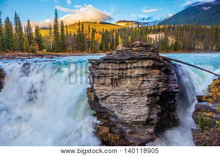 Powerful and scenic Athabasca Falls. Sunset illuminates the surrounding mountains. Canada, Jasper National Park