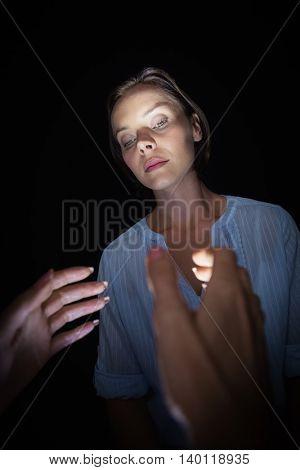 Cropped image of hypnotist hypnotizing woman against black background