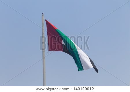 flag of UAE in Sharjah over blue sky