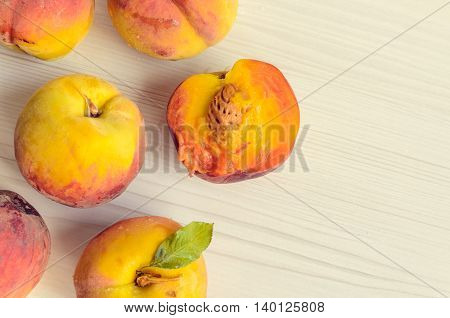 Ripe peaches on white wooden background. Group of fresh peaches on white table. Juicy and fresh peach with place for text. Concept for healthy eating and nutrition. Top view. Copy Space.