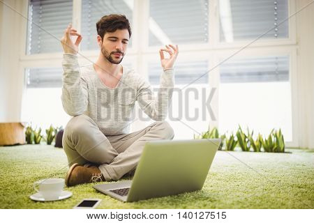 Young businessman doing yoga in front of laptop in creative office