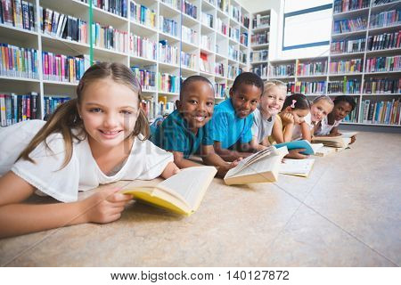 Smiling school kids lying on floor reading book in library at elementary school