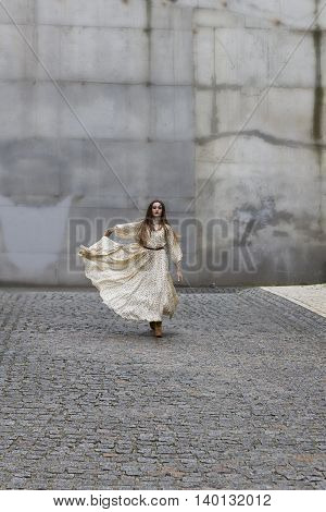 Girl in a long dress running on the street on a background of gray wall. Boho style. Outdoors.