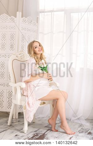 Portrait of beautiful pregnant woman. Blonde girl holding flowers posing in nightgown sitting on chair lovely looking at camera in white room. Indoor shot against window.
