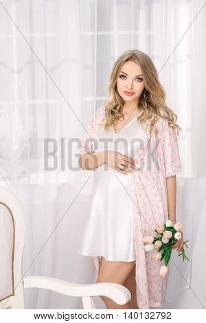 Portrait of beautiful pregnant woman. Blonde girl holding flowers posing in nightgown lovely looking at camera in white room. Indoor shot against window.