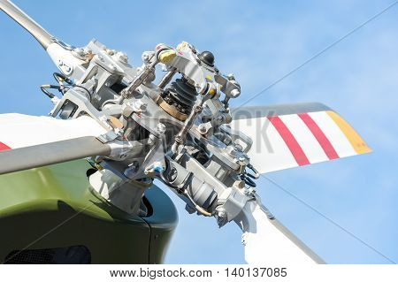 close-up of helicopter tail rotor blades against a blue sky