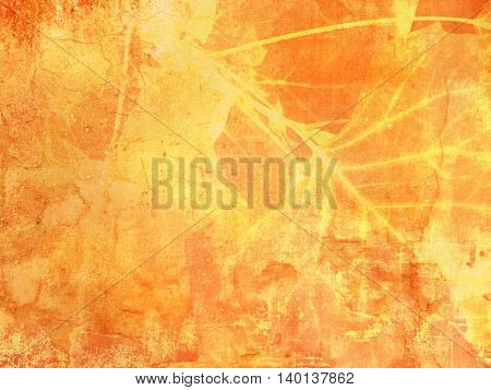 Grunge background texture in yellow orange fall colors with abstract leaves