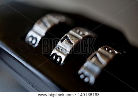 Macro detail of a black numerical combination lock with a silver number dial