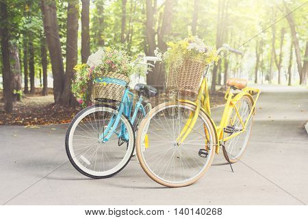 Two yellow and turqoise city woman bikes with flowers in park. Bright lady bicycles vintage style with baskets full of wildflowers in summer sunny town. Elegant recreational vehicles