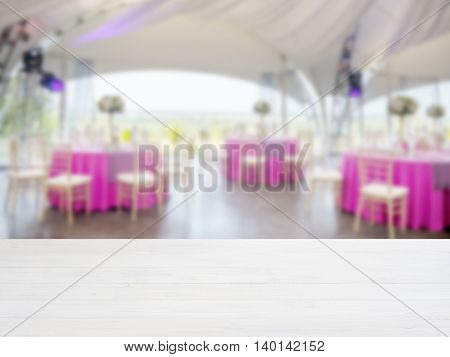 White wooden empty table in front of blurred restaurant interior background. Perspective white wood board over blur in restaurant or cafe - mockup for display or montage your products