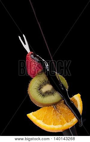 image of chocolate dipped fruits on black background