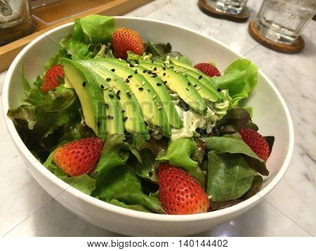 Closeup heathy avocado strawberry salad top with sesame with blur bokeh wooden tray and glass background