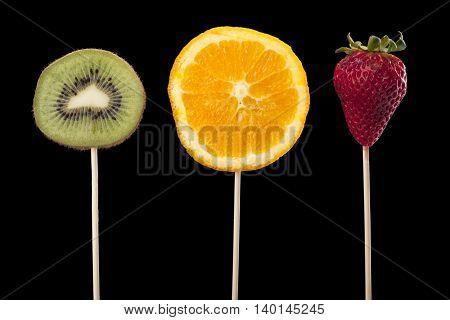 fruits on stick isolated on black background
