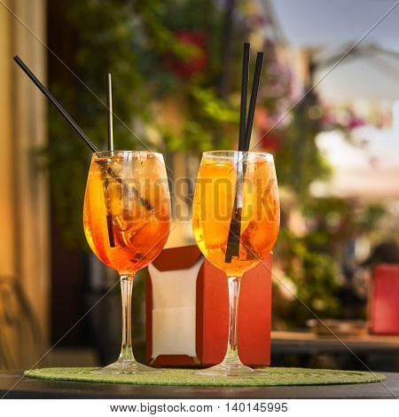 Aperol Spritz Cocktail. Alcoholic beverage based on table with ice cubes and oranges.