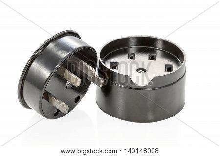 Black ceramic three-phase socket and plug lying beside isolated on white background