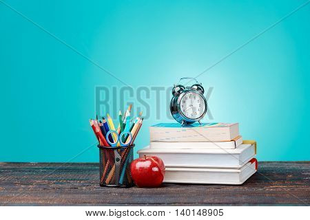 Back to School concept.School Books, colored pencils and clock on blue background