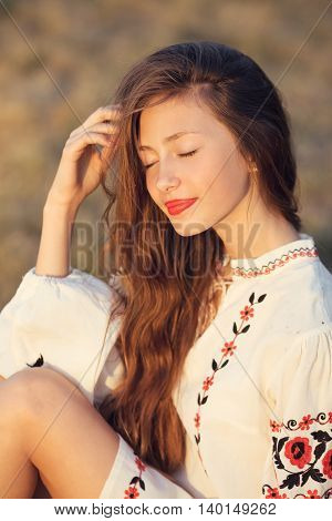 Slav teen girl portrait. Happy woman sitting on yellow meadow in national ukrainian clothing.