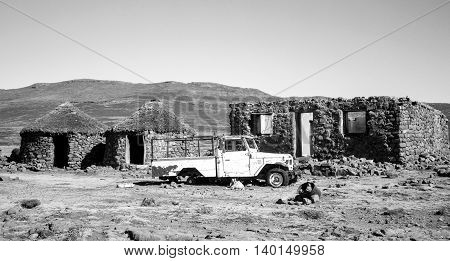 Abandoned car and ethnic traditional African houses rondavels next to the Sani Pass Kingdom of Lesotho. Drakensberg. Artistic retouching.