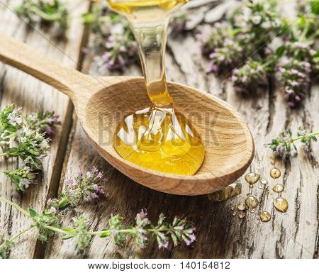Herbal honey pouring into the wooden spoon. Spoon is on old wooden table surrounded with lavender flowers.