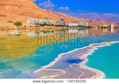 Emerald water of the Dead Sea. Fused salt made on the surface of the water