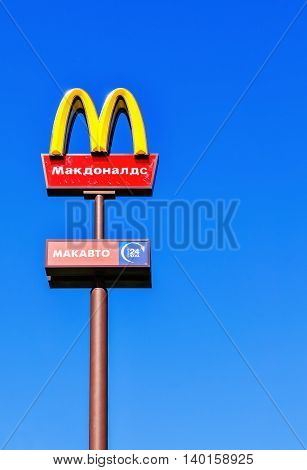 VELIKY NOVGOROD RUSSIA - MAY 5 2016. McDonalds logo against blue sky with Mc Drive inscription in Russian. McDonalds is the world's largest chain of hamburger fast food restaurants.