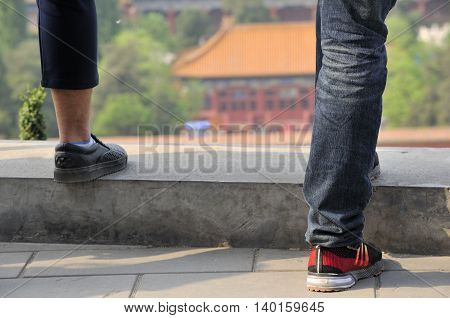 the lower legs of two men standing on a wall with a blurred background of a chinese building within Jingshan Park in Beijing China.