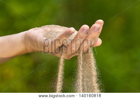 sand running through hands on blurred background